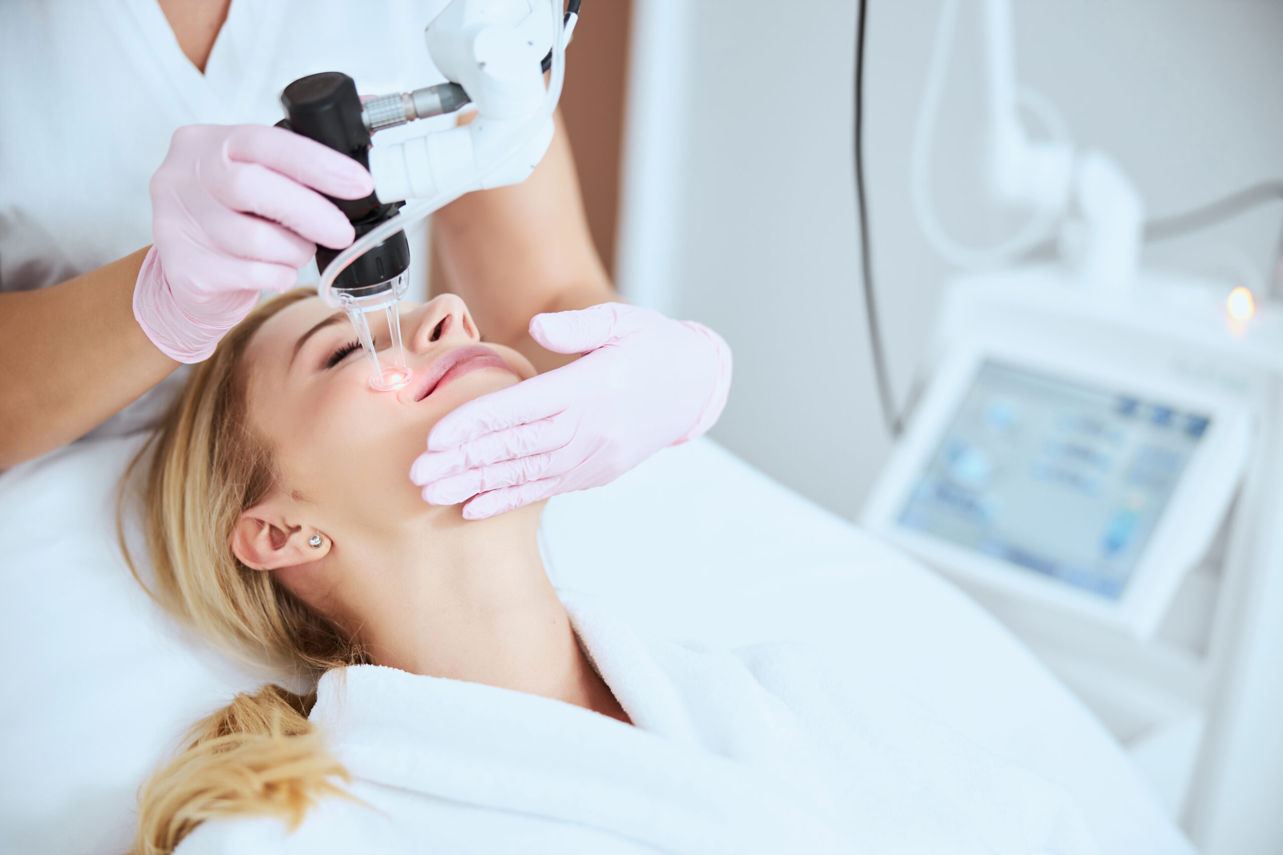 Pleased young Caucasian female undergoing the fractional carbon dioxide laser treatment in a beauty clinic